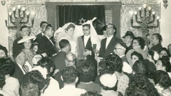 والتقط هذه الصورة أحد ضيوف حفل زفاف هذا العريس، غابي تمام، على عروسه لينا إيليني في المعبد عام 1958، ويظهر فيها الحاخام الباز وهو يتلو مباركته ممسكا بكأس من النبيذ.