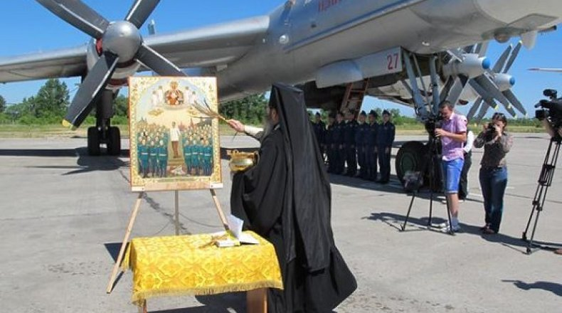 كاهن من الكنيسة الروسية يبارك الطائرات الروسية