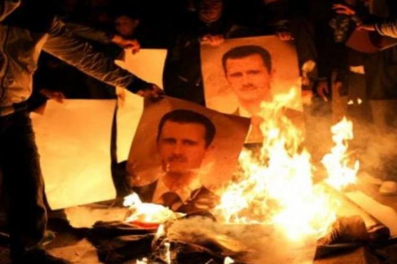 """إحراق صورة للإرهابي """"بشار"""" وكتابات مناهضة بريف دمشق"""