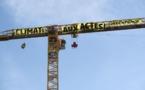 """ناشطون من """"جرينبيس"""" يعلقون لافتة ضخمة على رافعة ترميم نوتردام"""